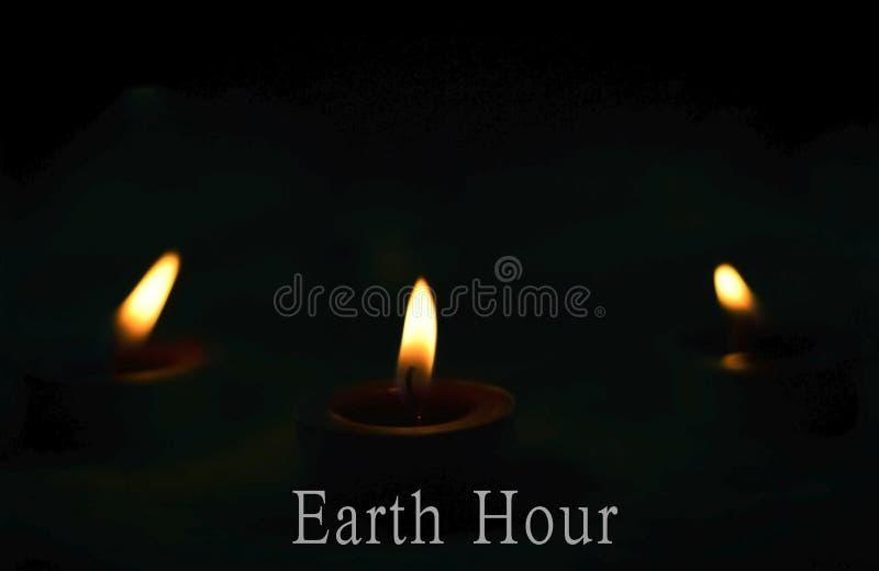 Concept d'heure de la terre : les bougies brûlent brillamment sur le fond foncé photo stock