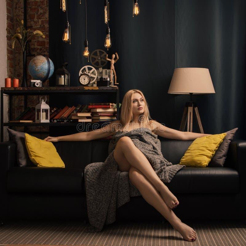 Concept d'hiver - jeune femme s'asseyant sur le sofa dans la couverture photo stock
