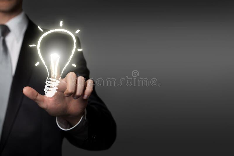 Concept d'idée d'affaires - homme d'affaires appuie sur le bouton virtuel d'interface d'écran tactile - ampoule rougeoyante photo libre de droits