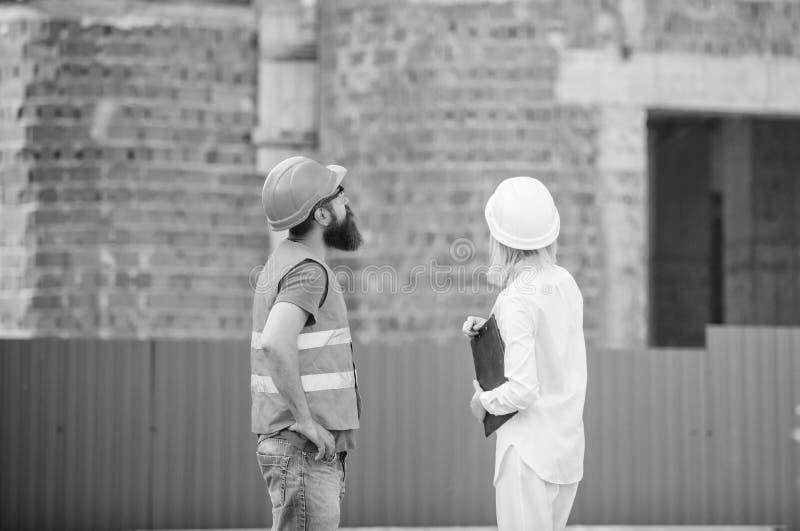 Concept d'industrie du bâtiment Ingénieur de femme et constructeur brutal barbu discuter le progrès de construction construction images libres de droits
