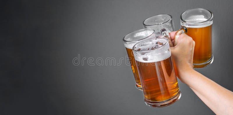 Concept d'Oktoberfest - remettez tenir des verres avec de la bière photos stock
