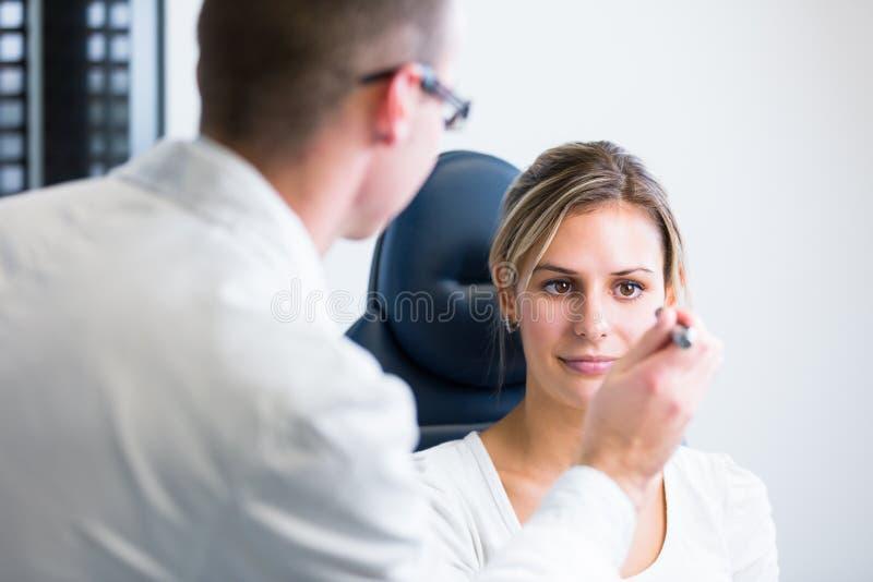 Concept d'optométrie - jolie jeune femme faisant examiner ses yeux photo stock