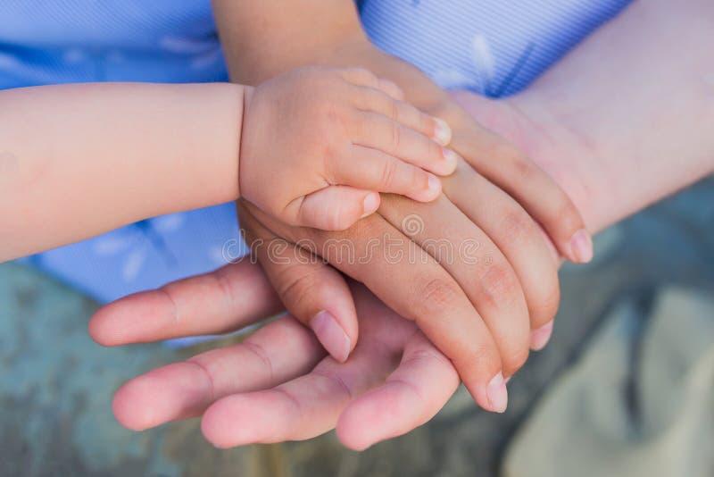 Concept d'unité, de soutien, de protection, de bonheur. Coupée de la main de l'enfant aux parents. Les mains du père, de la mè image stock
