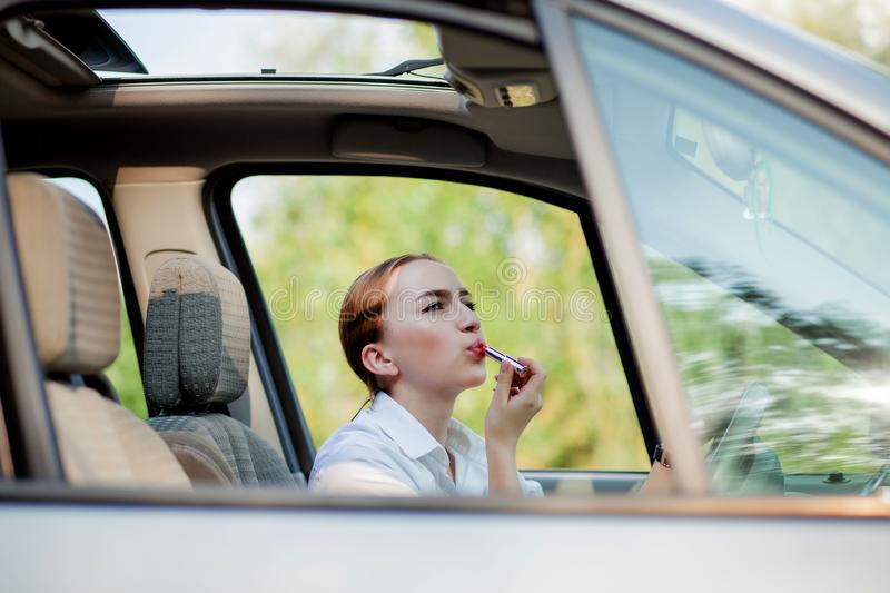 Concept of danger driving. Young woman driver red haired teenage girl painting her lips doing applying make up while driving the stock images
