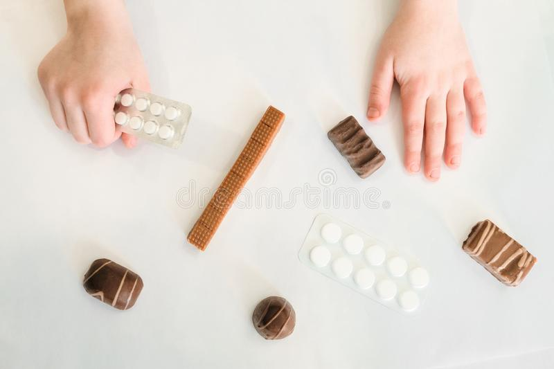 Concept of the dangers of sweets and sugar. Child holds in hand a pack of pills in his hand and reaches for sweets. royalty free stock photography