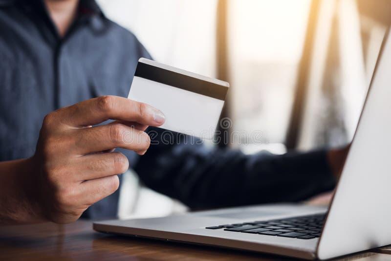 Concept de achat en ligne avec la main de l'homme utilisant l'ordinateur portable et regarder la carte de crédit pour le produit  image stock