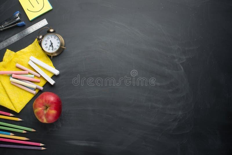Concept de bannière de nouveau au réveil d'école, papeterie de carnet d'Apple de crayon sur le fond de tableau noir Accessorie de photo stock