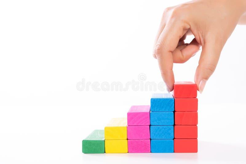 Concept de base de succès de bâtiment Les femmes remettent les blocs en bois mis sous forme d'escalier photos stock