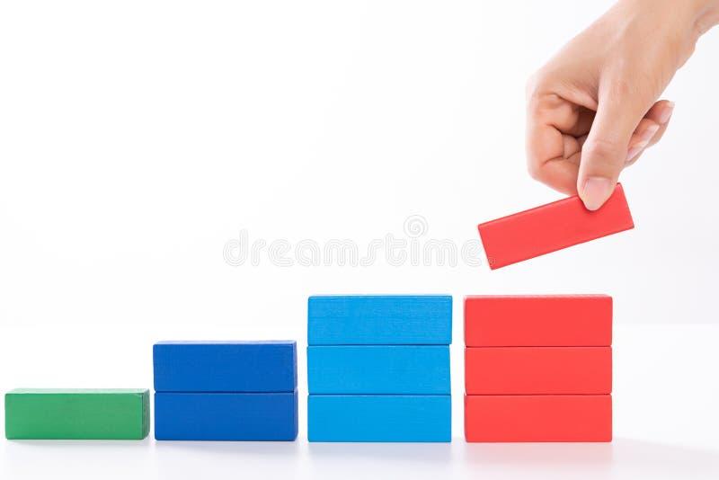 Concept de base de succès de bâtiment Les femmes remettent les blocs en bois mis sous forme d'escalier image libre de droits