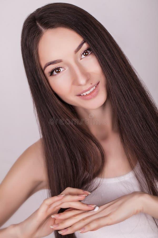 Concept de beauté, de personnes, de soins de la peau et de cosmétiques - femme heureuse avec le pot crème au-dessus du fond clair image stock