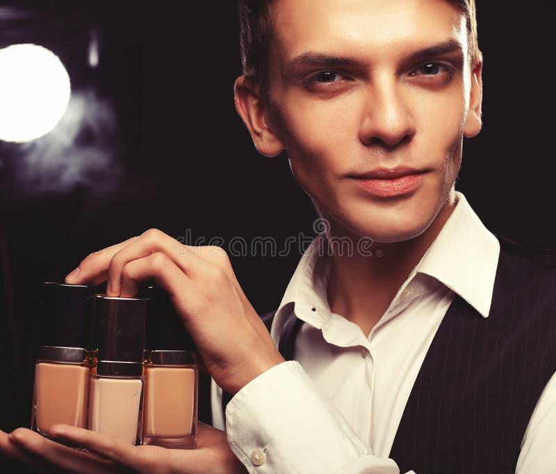 Concept de beauté Le jeune mâle composent l'artiste posant avec la base pour le maquillage sur un fond foncé image libre de droits