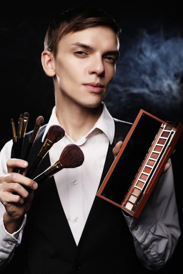 Concept de beauté Le jeune mâle composent l'artiste posant avec les brosses de maquillage et la palette d'ombre photographie stock libre de droits