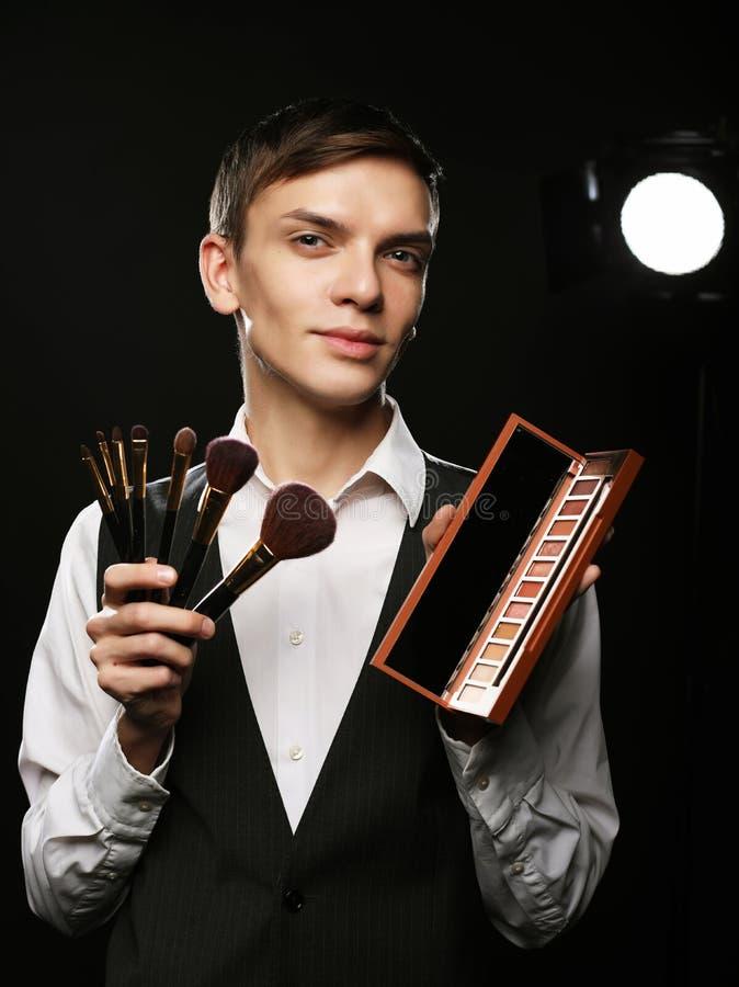Concept de beauté Le jeune mâle composent l'artiste posant avec les brosses de maquillage et la palette d'ombre photographie stock