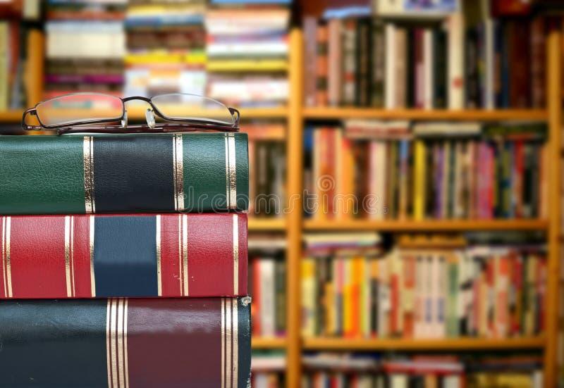 Concept de bibliothèque - livres et verres contre des étagères à livres photo stock