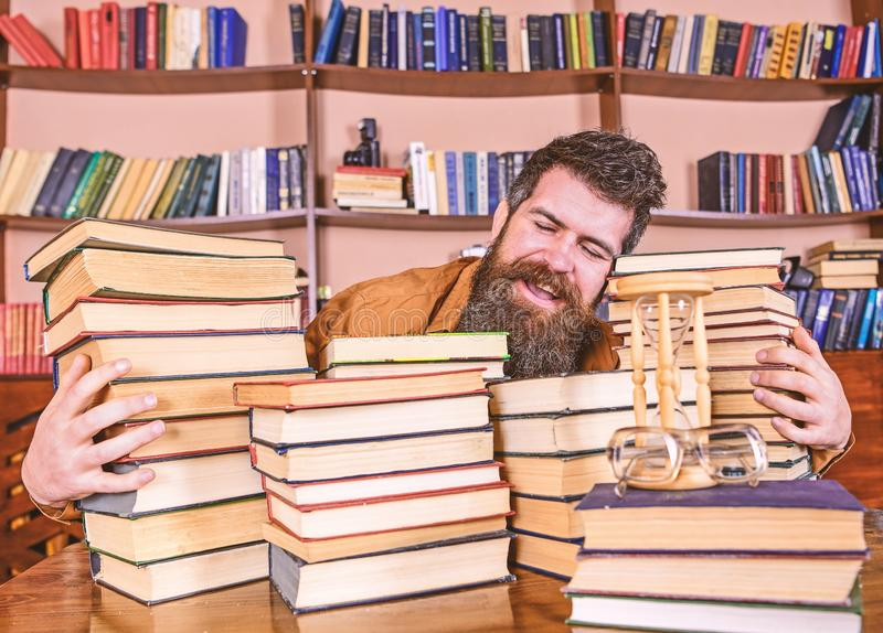 Concept de biblioth?caire Homme sur le visage heureux entre les piles des livres, tout en ?tudiant dans la biblioth?que, ?tag?res images libres de droits