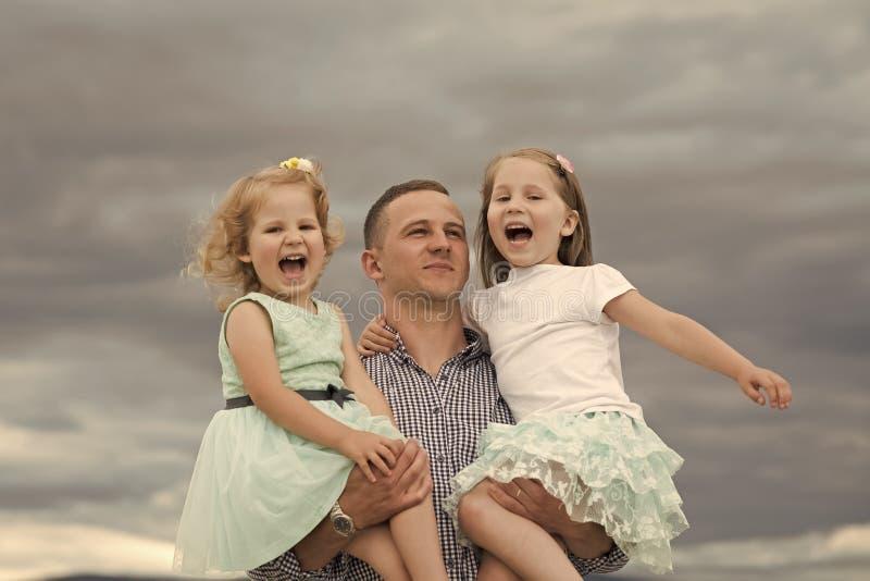 Concept de bonheur d'enfants d'enfance d'enfant Filles de prise de père sur le ciel gris nuageux images stock