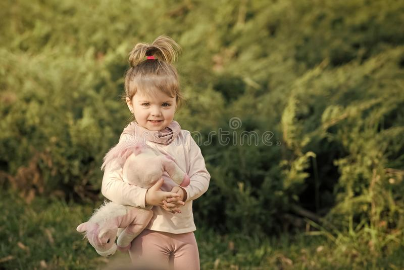 Concept de bonheur d'enfants d'enfance d'enfant La fille avec les cheveux élégants et le jouet sourient sur le fond naturel photos libres de droits