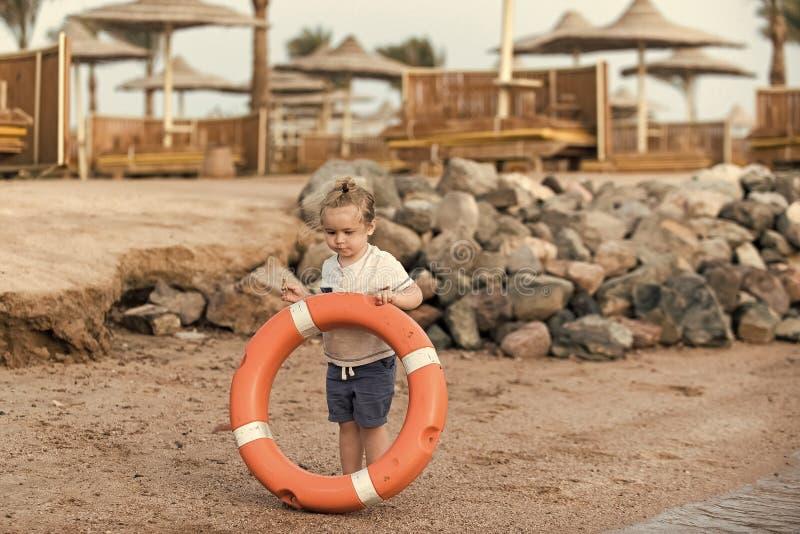 Concept de bonheur d'enfants d'enfance d'enfant Petit enfant de garçon tenant l'épargnant orange d'anneau à la côte photos stock