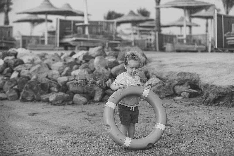 Concept de bonheur d'enfants d'enfance d'enfant Petit enfant de garçon tenant l'épargnant orange d'anneau à la côte image libre de droits