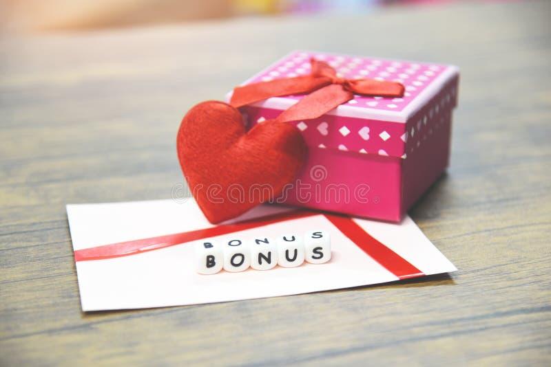 Concept de bonification/bonification annuels de carte dans l'enveloppe de papier avec la surprise de boîte-cadeau et le coeur rou photographie stock