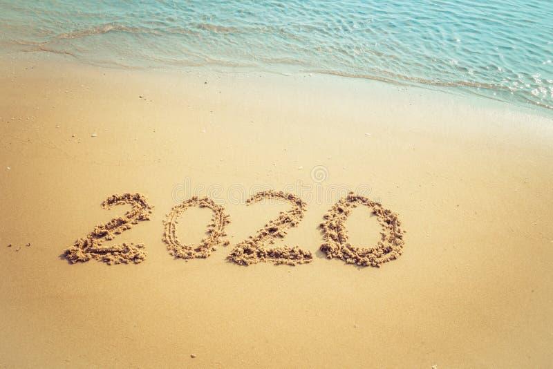 Concept 2020 de bonne ann?e, lettrage de 2020 nombres sur la plage de mer, vague et lumi?re d'or de coucher du soleil photographie stock