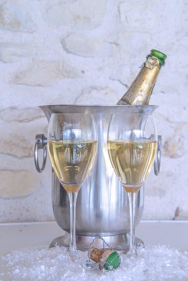 Concept de célébration : deux verres de champagne et de bouteille de cru dans le seau photographie stock libre de droits