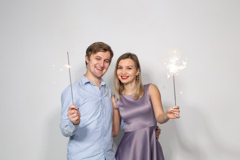 Concept de célébration, de partie et de vacances - homme heureux et femme étreignant au-dessus du fond gris avec des cierges magi photographie stock