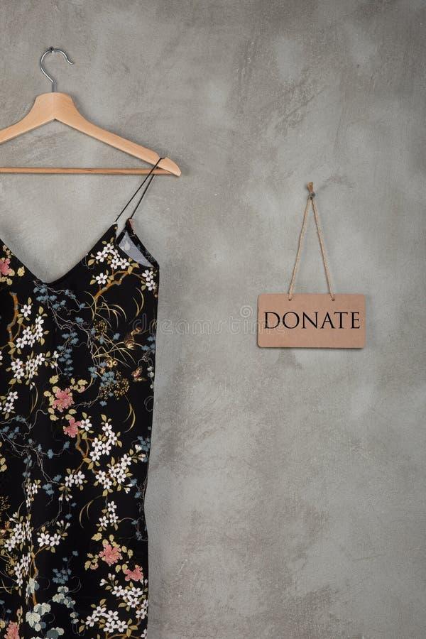 Concept de charité - le tableau noir avec le texte donnent et belle robe dans le modèle floral sur un cintre photo stock