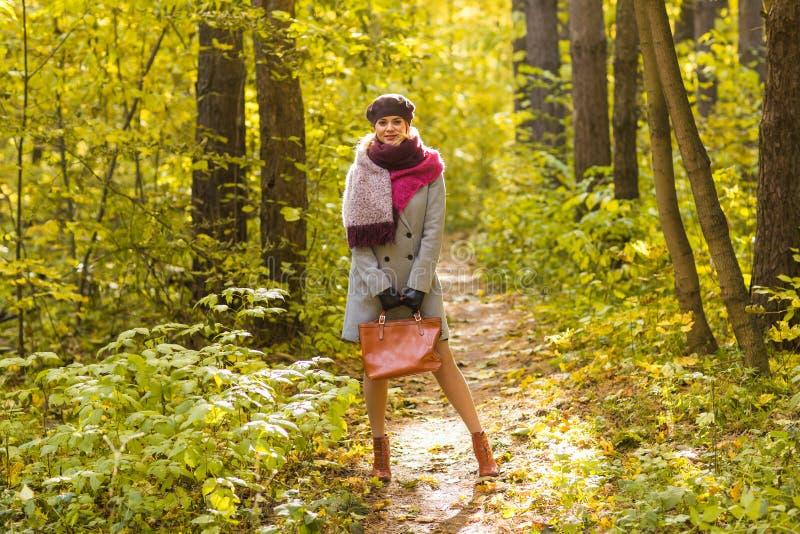 Concept de chute, de nature et de personnes - jeune belle femme dans le manteau gris se tenant en parc d'automne photo libre de droits