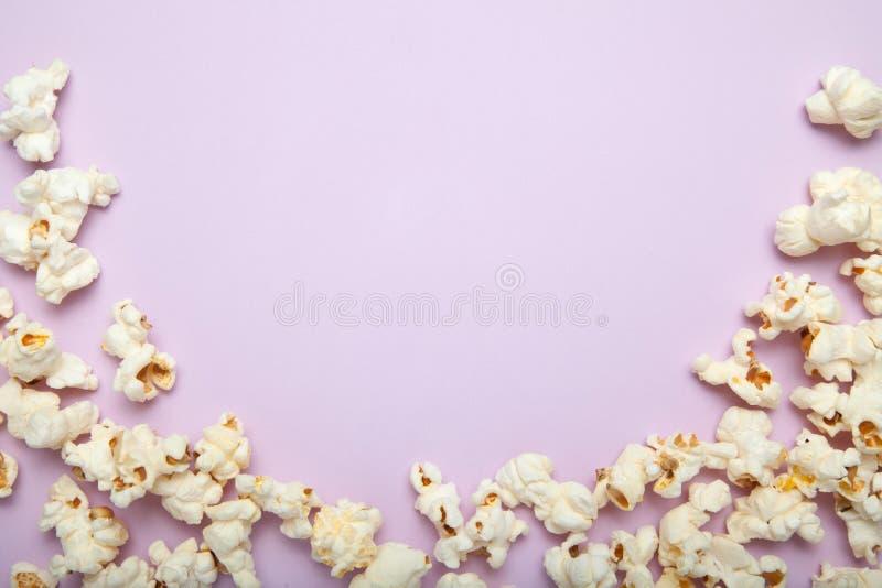Concept de cinéma avec des beaucoup maïs éclaté pelucheux sur le fond rose avec l'espace de copie image stock