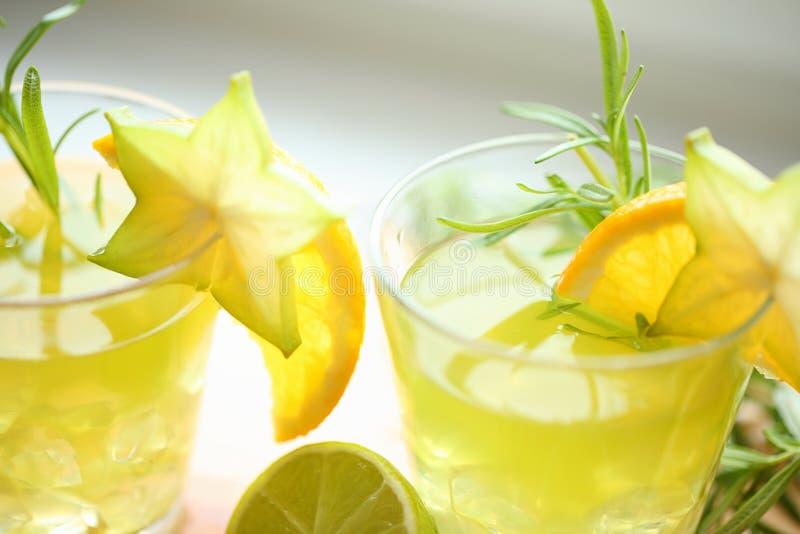 Concept de cocktails - standink vert de trois cocktails sur le bois, décoré de l'orange, du carambolier, de la chaux et du romari image stock