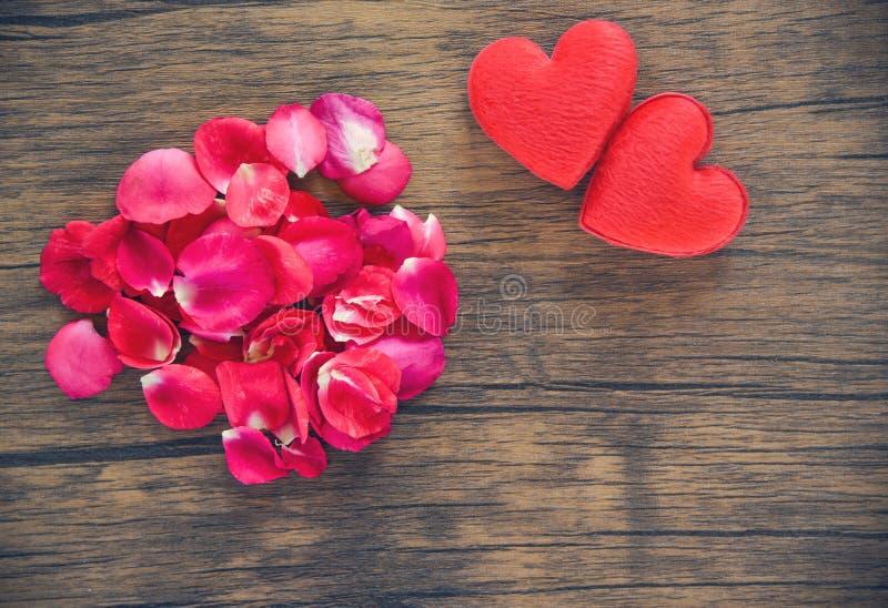 Concept de coeur d'amour de jour de valentines/pile des pétales de roses avec le coeur rouge décoré sur la table en bois photos stock