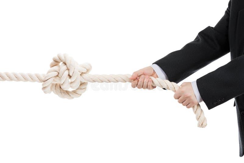 Main d'homme d'affaires se tenant ou corde de traction avec le noeud attaché image stock