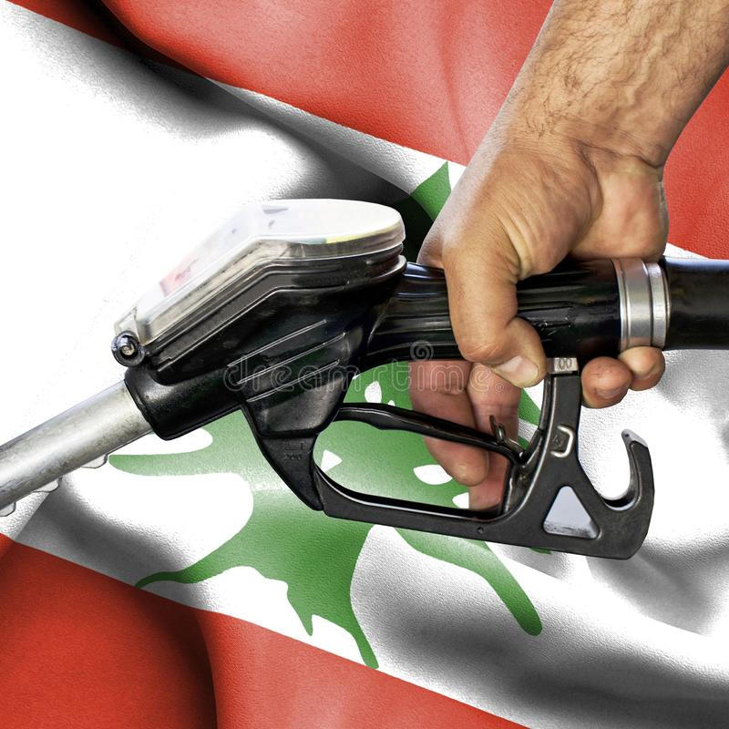 Concept de consommation d'essence - tuyau de participation de main contre le drapeau du Liban photo libre de droits
