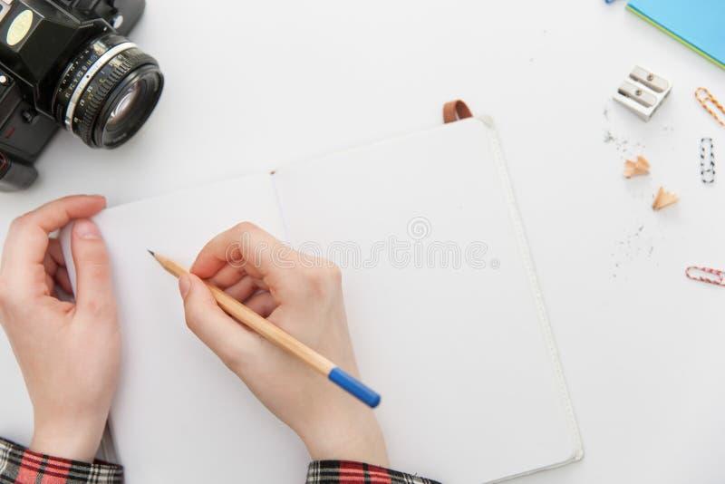 Concept de construction - vue supérieure de crayon de participation de main de page vide et de femme de carnet sur le fond blanc  photographie stock libre de droits
