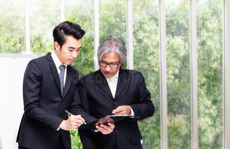 Concept de contact Deux documents iscussing d'homme d'affaires asiatique en main dans le bureau images libres de droits