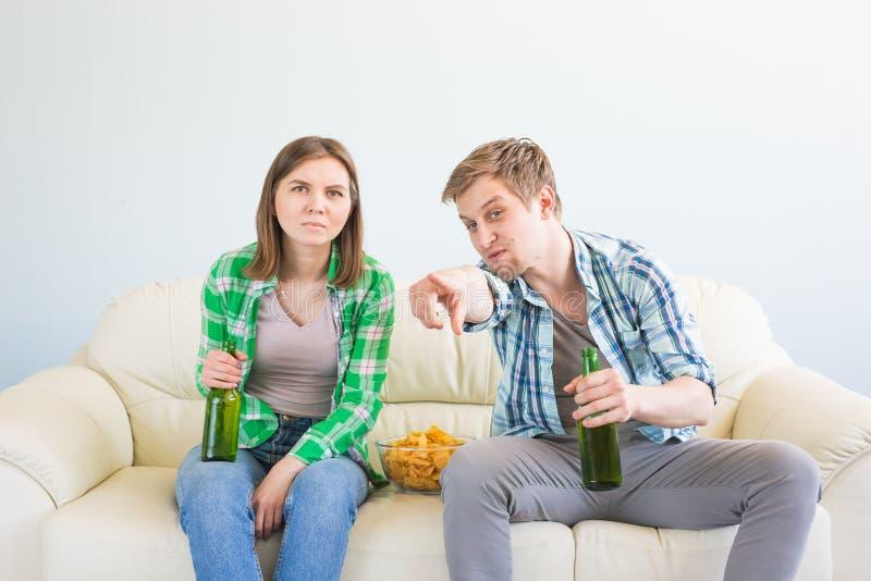 Concept de coupe du monde du football - couple des amis s'asseyant dans le jeu de observation de sport de sofa à la TV photos libres de droits