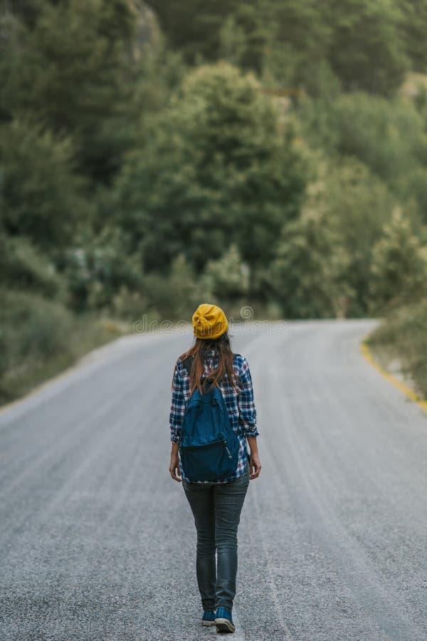 concept de course Femme de déplacement avec le sac à dos marchant sur la campagne de route goudronnée photo libre de droits