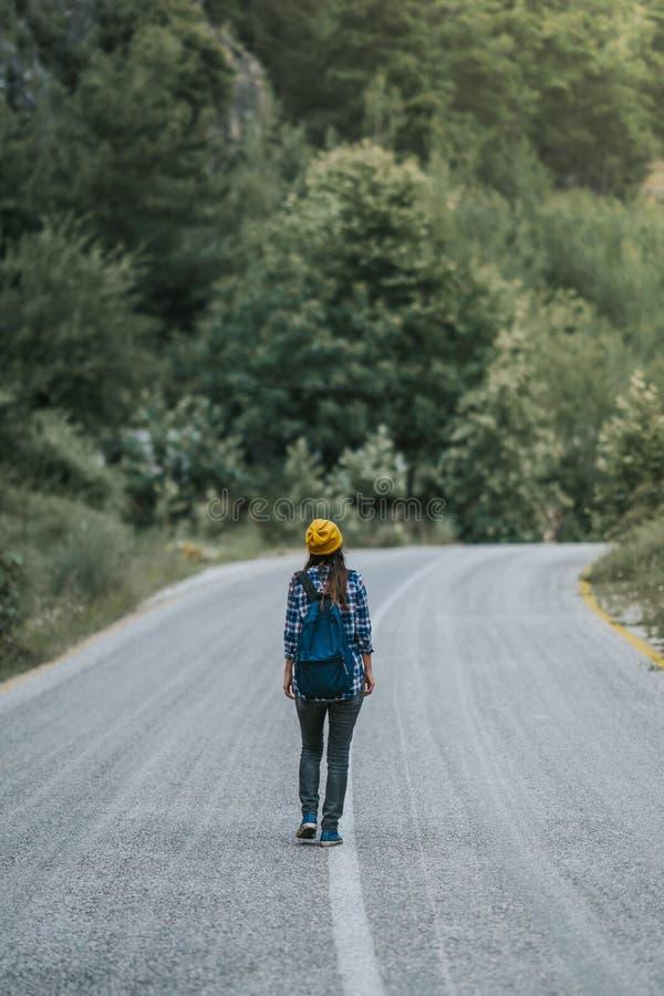concept de course Femme de déplacement avec le sac à dos marchant sur la campagne de route goudronnée image stock