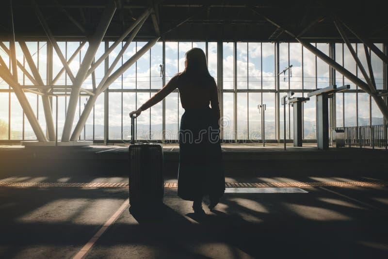 concept de course Jeune femme attendant avec la valise sur la plate-forme à la gare ferroviaire photo stock
