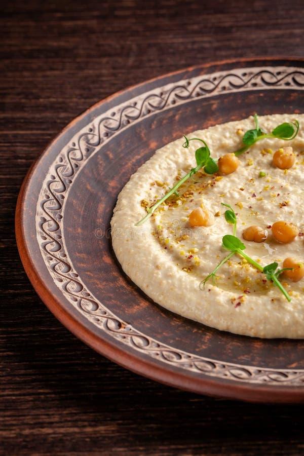 Concept de cuisine arabe Houmous oriental avec le sésame et les pistaches grillés Un plat dans un restaurant dans un plat en céra images stock
