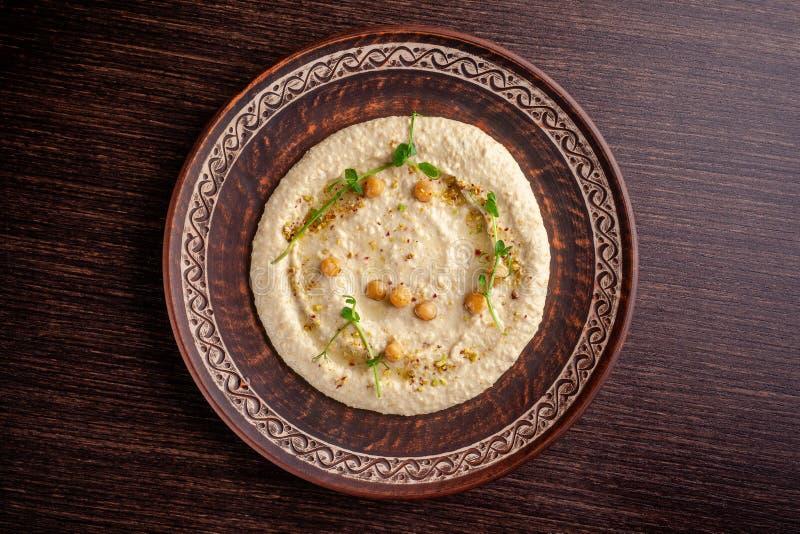 Concept de cuisine arabe Houmous oriental avec le sésame et les pistaches grillés Un plat dans un restaurant dans un plat en céra photo libre de droits