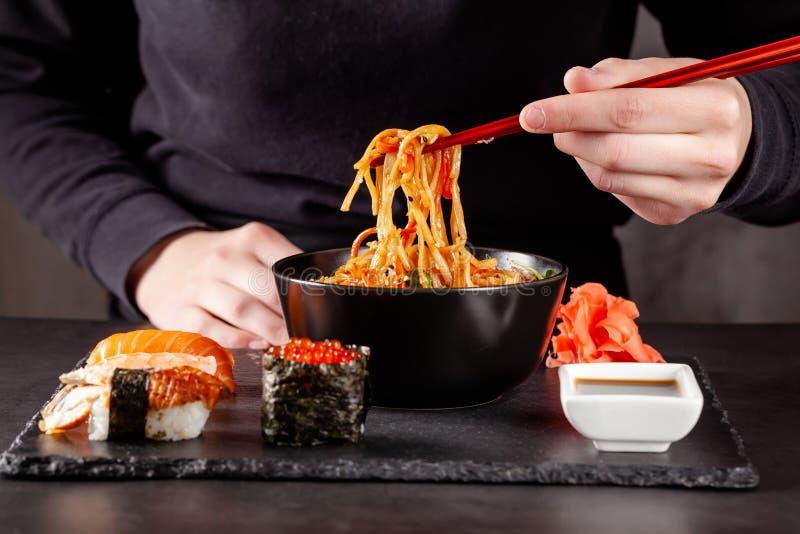 Concept de cuisine asiatique La fille tient les baguettes japonaises dans sa main et mange les nouilles chinoises d'un plat noir image libre de droits