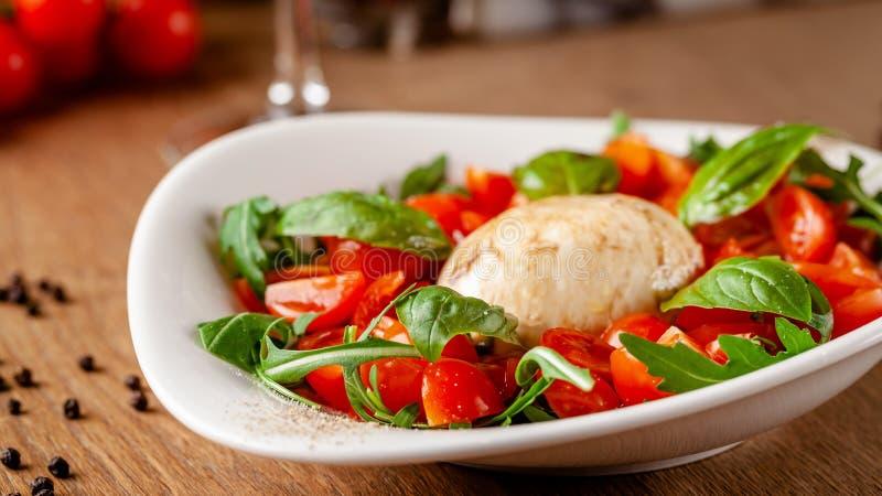 Concept de cuisine italienne Salade de Caprese avec les tomates-cerises, le mélange d'arugula et de salade de basilic, et le from photo stock