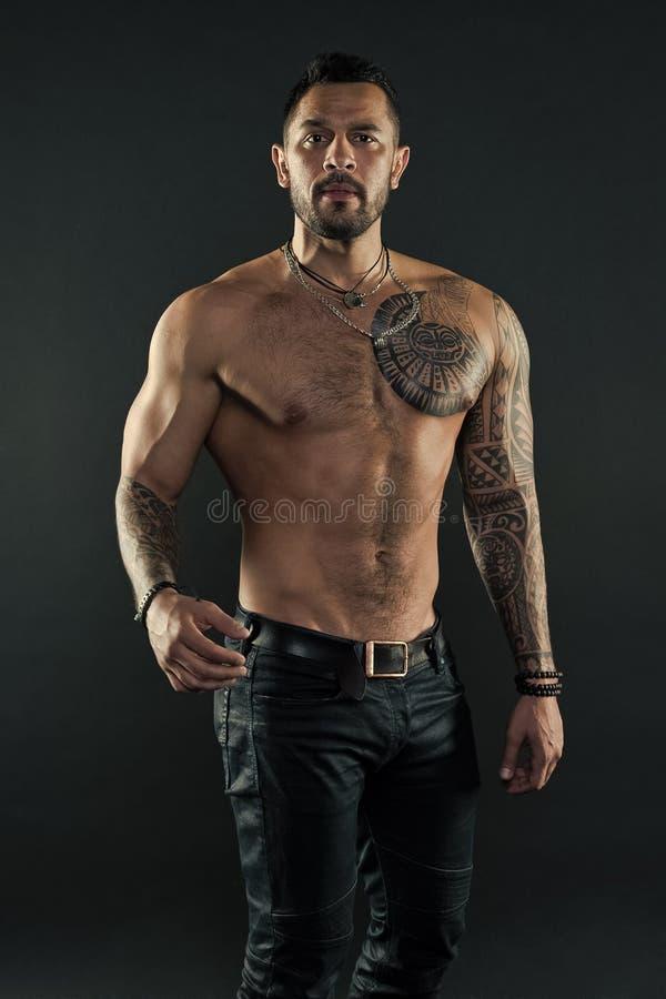 Concept de culture de tatouage Attribut brutal de tatouage L'aspect hispanique non ras? brutal d'homme a tatou? des bras Expositi photographie stock