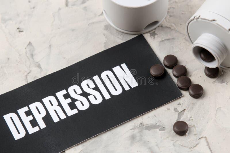 Concept de dépression Maladie psychologique la dépression de mot sur le papier et les pilules sur un fond clair Vue supérieure photographie stock libre de droits