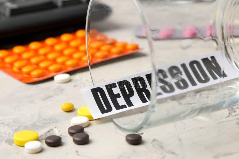 Concept de dépression Maladie psychologique la dépression n de mot et pilules sur un fond clair photo stock