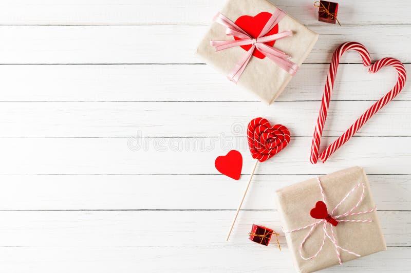 Concept de dag van Valentijnskaarten Het hart vormde suikergoed en giftvakjes op een witte houten achtergrond met exemplaar ruimt stock afbeeldingen