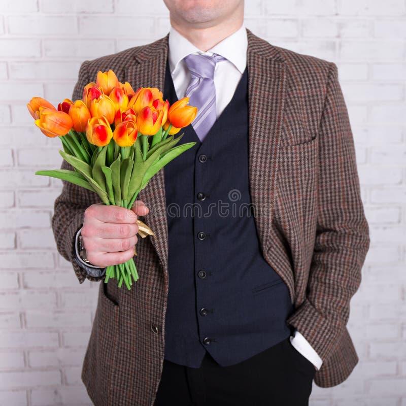 Concept de datation - fermez-vous des fleurs dans des mains masculines image libre de droits