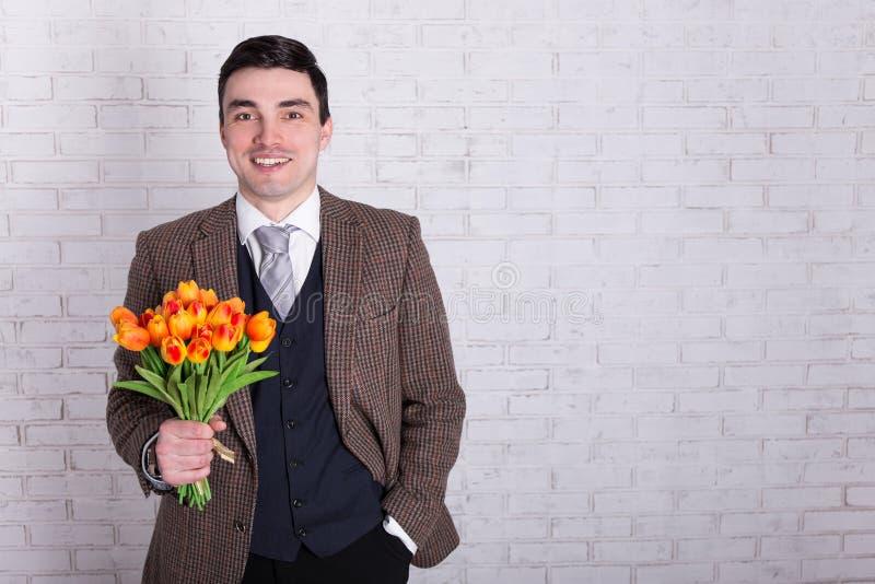 Concept de datation - jeune homme avec des fleurs au-dessus du mur blanc image libre de droits